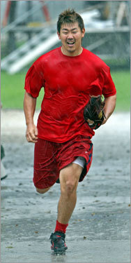 Daisuke Matsuzaka runs off the field after a practice as rain comes down around him.