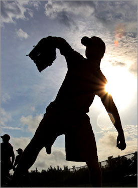 Jon Lester is silhouetted as he winds up to throw.