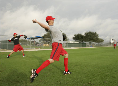 Clay Buchholz (right) and Manny Delcarmen wind up to throw while working out on the field.