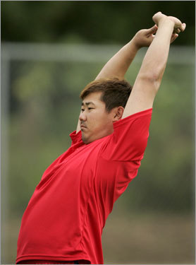 Matsuzaka stretches while working out on the field.