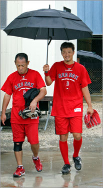 After he worked out in the indoor batting cages, Red Sox reliever Hideki Okajima (right) protected both himself and translator Jeff Yamaguchi from the rain as they headed from there to the clubhouse.