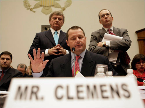Former New York Yankees pitcher Roger Clemens (center) gestures as his attorney's Rusty Hardin (left) and Lanny Breuer (right, standing) try to address members questions during testimony on Capitol Hill. (Some text from the Associated Press)