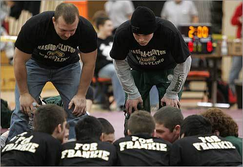 Nashoba Valley High School coach Matt Schiller (left) huddled with his wrestlers before a meet at Marlborough High School on Feb. 9. Frank Medeo, of one of the wrestlers from Nashoba, died a week earlier when he was run over by a car while jogging.