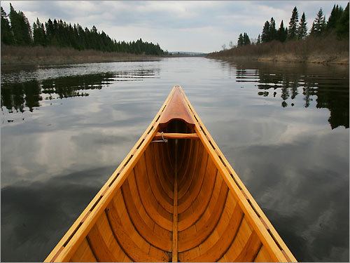 A wood canvas canoe heads down the Big Black River, an infrequently canoed river in northern Maine.