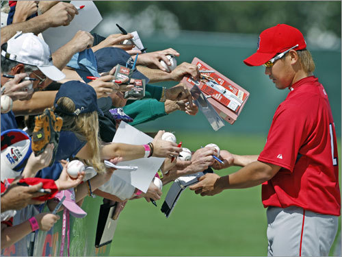 Red Sox pitcher Daisuke Matsuzaka attracted a crowd as he signed autographs for fans on his way off the field following Tuesday's workout.