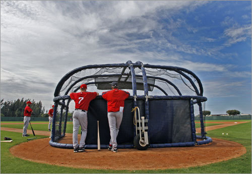Red Sox outfielder J.D. Drew (7) and hitting coach Dave Magadan chat behind a batting cage.