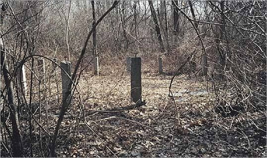 Rebecca Duda wants Dracut officials to reclaim the Claypit Cemetery (above). The town's oldest burial ground, it lies in ruins behind a bowling alley.