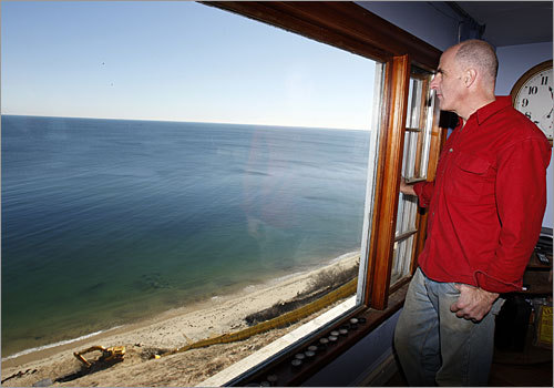 Kevin Donovan looks at his view of the Atlantic Ocean from his living room, which inspired him to buy the Plymouth home last year. However, the purchase had a risk: The Cape-style house was about to topple over a 200-foot sandy bluff and into the ocean below.