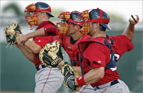 Who are those masked men? Red Sox catchers (from left) Zak Farkes, Dusty Brown and Jason Varitek threw together during a drill Monday morning.