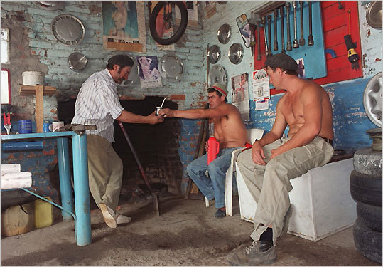 Duron Claudio passes a cup of hot mate, or herbal tea, to a friend visiting their roadside gomeria. Juan Loty (right) watches. The men are taking a break on a slow, sunny morning.