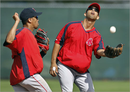Shortstop Julio Lugo (left) backs off just in time as second baseman Alex Cora (right) makes the catch during a high pop up drill during Tuesday's workout.