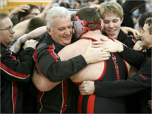Winchester head coach Larry Tremblay (center) hugs Andrew Zani after his win at 285 pounds punctuated Winchester's 48-18 win over Wayland in the Division 3 championship.