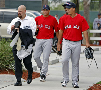 Kevin Youkilis (left) heads for one of the three waiting buses. As he does, he passes some minor league players who are heading for a workout.