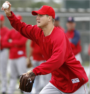 Jonathan Papelbon holds the baseball as he attempts to tag a base runner during pickoff drills.