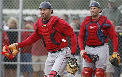 Jason Varitek (left) pulls off his mask as he and catcher Doug Mirabelli watch a pickoff play at third base.