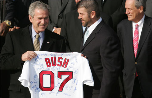 President Bush holds an autographed Boston Red Sox jersey presented to him by Jason Varitek (second from right) as he stands with members of the 2007 World Series Championship Boston Red Sox baseball team, including manager Terry Francona (right) and holding the World Championship trophy, David Ortiz (left), on the South Lawn of the White House.