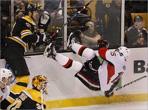 Boston Bruins' Zdeno Chara launches Ottawa Senators left wing Dany Heatley during a game.