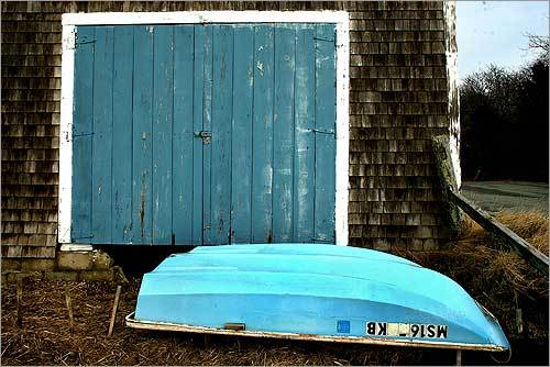 A dinghy lay in front of a boathouse off Sears Road at Stage Harbor in Chatham. Some Chatham residents are pushing to have the small boats removed from their docking locations offshore.
