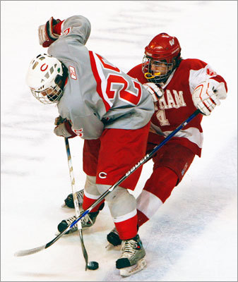 Catholic Memorial's Travis Jonasson (25) battles for possession of the puck with Waltham's Billy Keating.