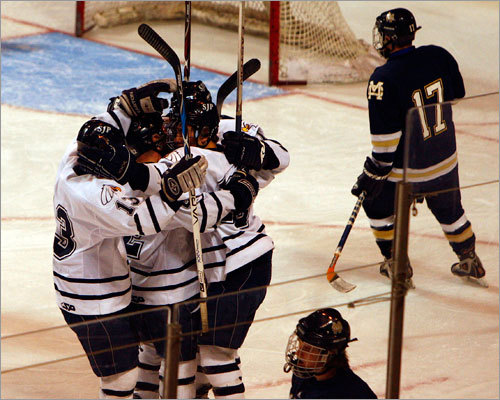St. John's Prep players gather around Christian Cowles (10) after his first-period goal.