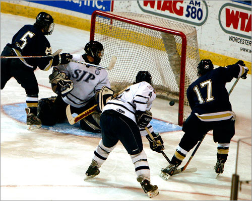 With Malden Catholic forwards Andrew Cerretani (5) and Zack Sheppard (17) at the crease, St. John's Prep goalie Kyle Pettoruto can't see the blast fired by Craig Carbonneau (not pictured) for a second-period goal.