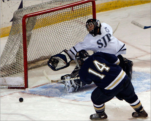 St. John's Prep goalie Kyle Pettoruto stretches for the puck as Malden Catholic forward James Castrucci (14) rushes in.