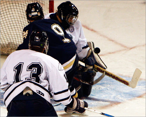 Malden Catholic forward Craig Carbonneau (9) watches as St. John's Prep goalie Kyle Pettoruto makes the save as defenseman Eddy Estey (13) patrols in front of the net.