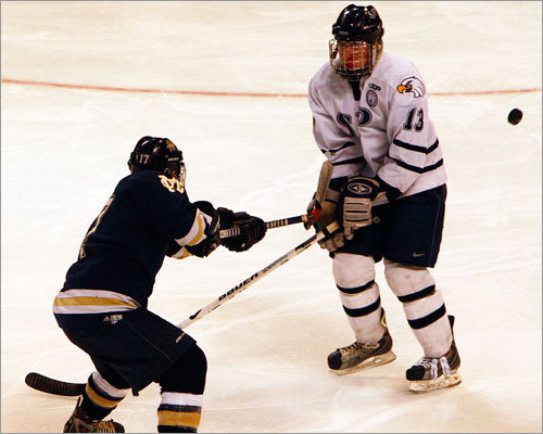 Malden Catholic forward Zack Sheppard (17) drives the puck past St. John's Prep's Eddy Estey (13).