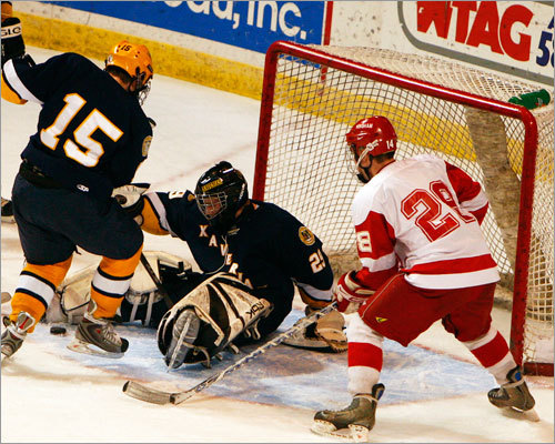 Xaverian defenseman Andrew White (15) kicks the puck with his skate to goalie Kyle MacDonald (29) as Hingham's Conor Leary (28) looks for a rebound.