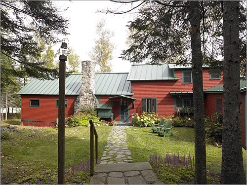 This large family retreat in the Rangeley Lakes region of western Maine was profiled by The Boston Globe Magazine. The home has undergone many changes over the years. It had previous incarnations as a tiny cabin and a summer camp. The home's red-green color scheme is typical for exteriors in the Maine woods.