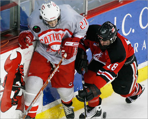 Catholic Memorial's Troy Starrett, left, fights for possession of the puck with Reading's John Michael Leach.