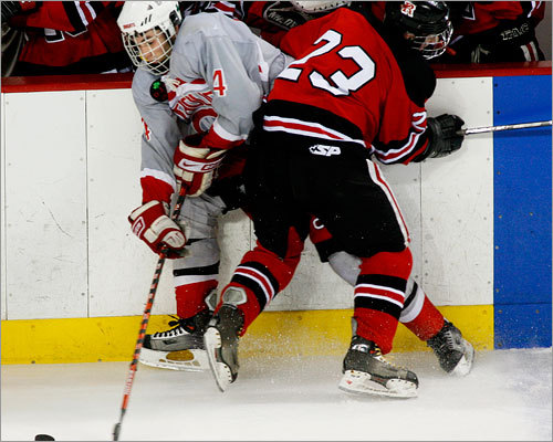 Catholic Memorial's Peter Starrett (4) fights for the puck with Reading's Jon Kaine.