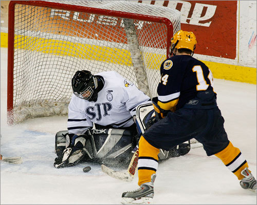 Xaverian's Chris Wagner (14) tries to push the puck past St. John's Prep netminder Kyle Pettoruto.