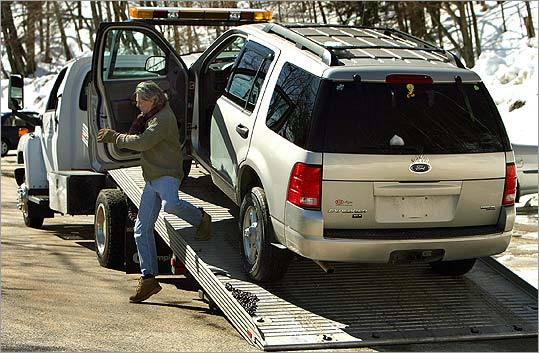 Tow truck operator Dana Williamson loaded a repossessed Ford Explorer in Peterborough, N.H., yesterday.