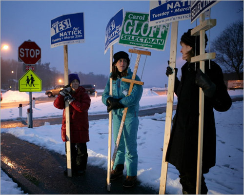 With at least 40 Eastern Massachusetts cities and towns planning to ask voters for more than $50 million over the next few months, thousands of young mothers have organized to persuade neighbors to vote themselves a tax hike. Shown here (from left) were Firkins Reed, Kim Schmid, and Mary McKenna, holding up placards recently outside Natick High School, urging community members to support a budget override.