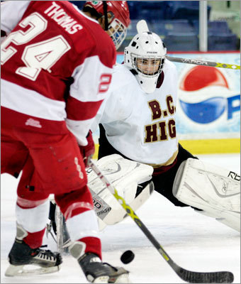 Waltham's Kyle Thomas tries to stuff home a loose puck as BC High netminder Sam Marotta protects the net.