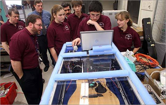 From left, teacher Steve Rugoletti looks on as students Kati Orban, Cody Jones, Anthony LoConte, and Rachel Nadler tune a guitar that will be used in the zero-gravity experiment. In back from left, teachers Lou Broad, Ron Edmiston, and Mark Cerniglia.