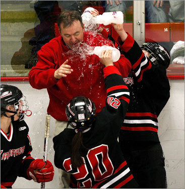 Hingham head coach Tom Findley gets a celebratory water bath from his players following a 6-1 victory over Milton.