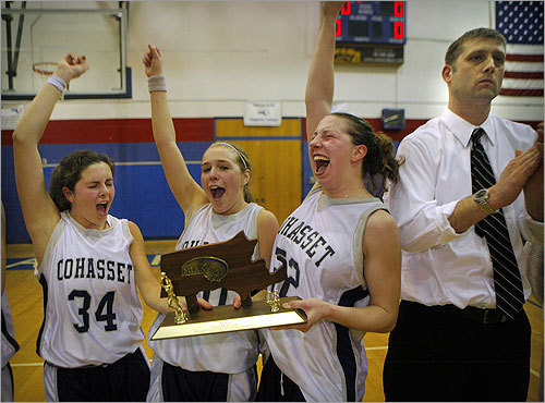 Cohasset girls basketball team members (from left) Kayla Farren, Carly Salerno, and Sammi Lehr celebrated their win over Millis after the South Sectional Division 4 Finals at Braintree High School. Coach John LeVangie at right.