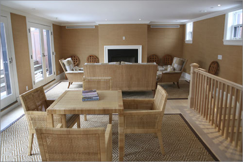 A look at the family entertainment room on the top floor. Decorated in tasteful yet distinctive neutral wallcoverings, with hardwood floors, imported tile, and designer wall-to-wall, this room is the unit's coziest feature, and includes a full kitchen, fireplace, and entry to a private 18-by-35-foot deck with a close-up view of the city skyline.