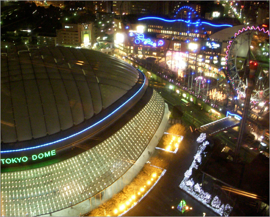 The Tokyo Dome Baseball Stadium, where the Red Sox open their season, is lit up like an alien craft at night.