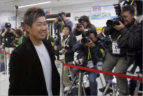 All eyes and cameras are on Red Sox pitcher Daisuke Matsuzaka (left) as he arrives at Tokyo's Haneda Airport.