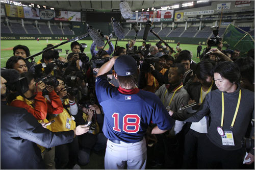 Red Sox starter Daisuke Matsuzaka (18) tips his cap as he arrives for his team's practice at theTokyo Dome.