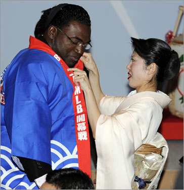 David Ortiz (left) is helped by a Kimono lady wearing Japan's traditional 'Happi' coat during the welcoming party at a Tokyo hotel on Friday.