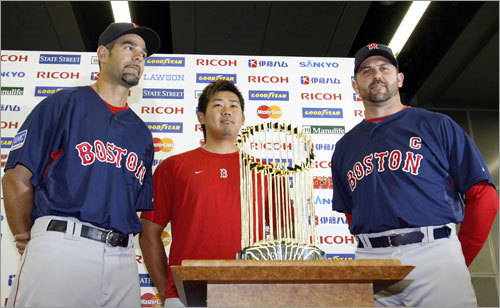 Red Sox infielder Mike Lowell, pitcher Daisuke Matsuzaka, and catcher Jason Varitek pose with their 2007 World Series trophy during a news conference in Tokyo on Friday.
