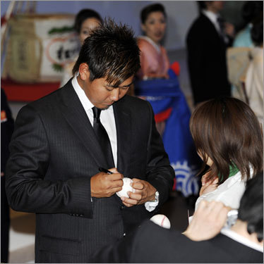 Red Sox Japanese pitcher Daisuke Matsuzaka signs his autograph on a ball during the welcoming party.