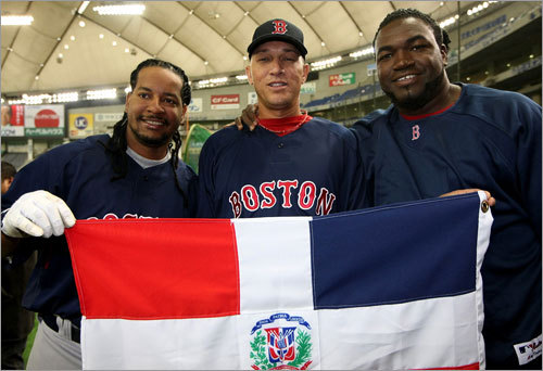 Outfielder Manny Ramirez, pitcher Julian Tavarez, and DH David Ortiz of the Red Sox hold the Dominican national flag before working out at the Tokyo Dome.