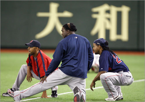 Red Sox infielder Alex Cora, David Ortiz, and Manny Ramirez stretch during the team's first workout on Friday.
