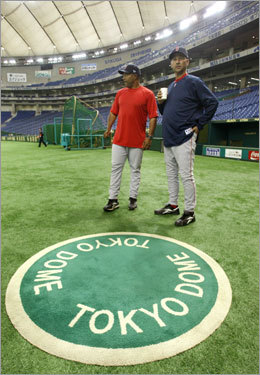 Red Sox manager Terry Francona (at far right) and third base coach DeMarlo Hale survey the field just prior to the start of the team's first workout in Japan.