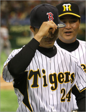 Hanshin Tiger outfielder Shinjiro Hiyama tried on his new Red Sox hat after the pregame hat exchange between the two teams.